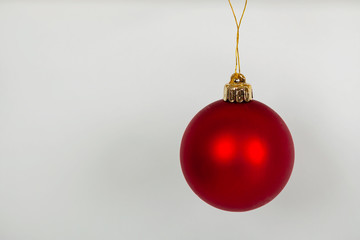 Hanging red Christmas bauble, against a white background