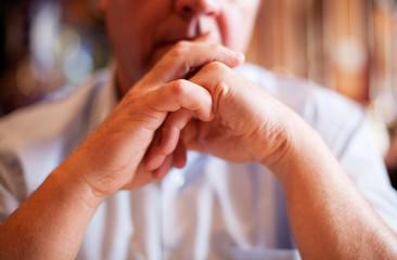 homme a l écoute mains jointes