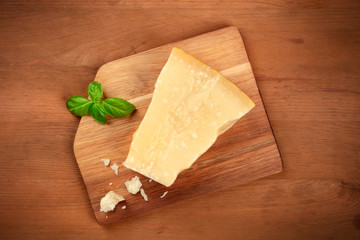 A piece of aged Parmesan cheese with crumbs and fresh basil, shot from the top on a dark rustic wooden background with a place for text