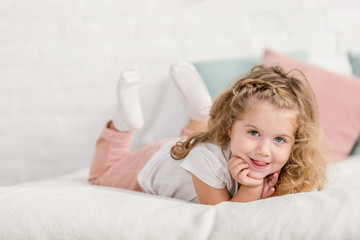 smiling adorable happy kid lying on bed in children room and looking at camera