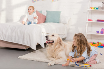 adorable preschooler pretending veterinarian and examining golden retriever in children room