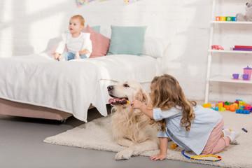 adorable kid pretending veterinarian and examining golden retriever in children room