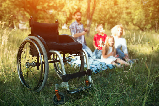 Focus on emply wheelchair on the foreground while happy family rest on the background