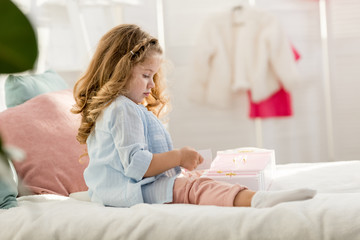 side view of adorable child playing on bed in children room