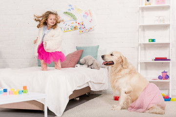 happy adorable kid jumping on bed, golden retriever sitting on carpet in pink skirt in children room