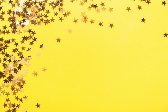 Golden shining stars confetti on yellow