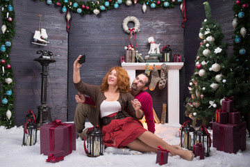 Full length of pleased mature couple making selfie against Christmas background