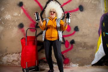 rebel grandma graffiti artist against a wall
