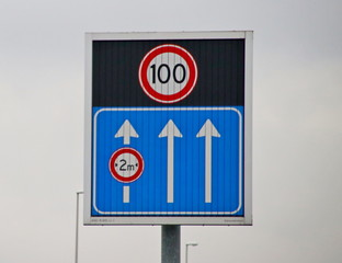 Arrows indicating the open driving lanes on motorway A12 with small lane 3 and dynamic speed limit sign of 100 kilometers