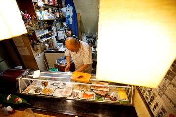 Masatoshi Fukutsuna, chef and owner of sushi restaurant Eiraku, and his wife Mitsue cook sushi dish at their restaurant in Tokyo
