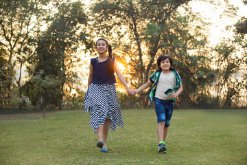 Happy brother and sister walking in park holding hands with sunlight in the background.