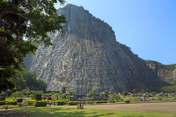 Tourists walk in the Park on the background of the rock of the Golden Buddha in the vicinity of Pattaya