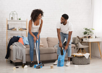 Man and woman cleaning messy room after party
