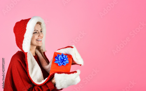 a426f28c965 Happy girl in santa hat holds Christmas present. Sensual woman in Santa  Claus hat with gift. Christmas