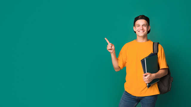 Teen student with books pointing on copy space