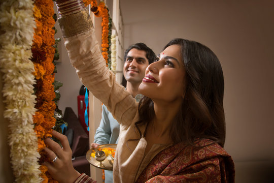 Close up of happy young couple in traditional dress decorating their home with flowers.