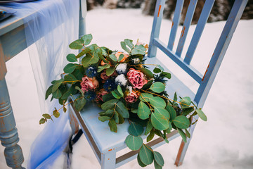 Pretty bouquet with pink roses, lying on chair against snowy mountains
