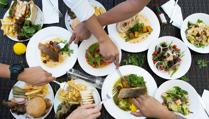 Mix Various Seafood, Spaghetti, club sandwich, burger, salad, hot spicy Foods on table over tropical ocean atmosphere, Top view camera dinner lunch together with friends family