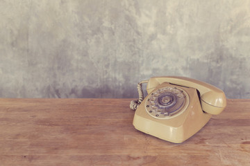 Vintage telephone on wooden table with cement wall background.