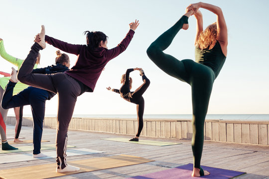 Group of young sporty people practicing yoga lesson, standing in Natarajasana exercise, Lord of the Dance pose, working out, outdoor, students training on wooden terrace at sunrise. Well-being concept