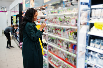 Stylish african american woman at green coat and yellow dreess posed at cosmetic store, buying make up accessories on beauty shop.