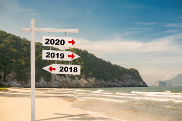 wooden sign with text 2020,2019 and 2018 Over Blurred blue sea and sand beach with cloudy blue sky , Image for New year 2019-2020 Concept,Copy space.