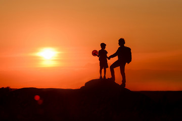 Dad and boy with balloon on fathers day travel together in mountains, beautiful sunset background. Father and son hold hands and look at each other, idyllic scene in evening landscape with setting sun