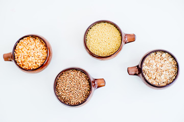 different types of groats in pots on a white background