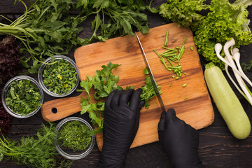 Hands in black disposable gloves cutting parsley