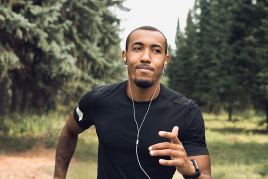 African-american man jogging and listening music outdoors