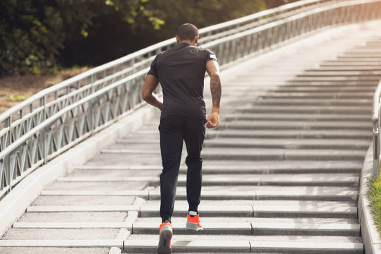 Morning workout. African-american man running up on stairs