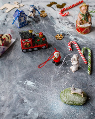 New Year's composition of vintage Christmas toys on a gray table with lollipop