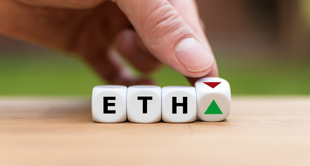 Hand is turning a dice and changes the direction of an arrow symbolizing that the value of the crypto currency Ethereum (ETH) is going up (or vice versa)