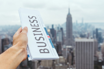 partial view of man holding business newspaper with blurry new york city view on background