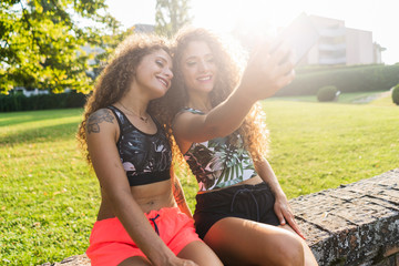 Smiling twin sisters taking selfie in a park
