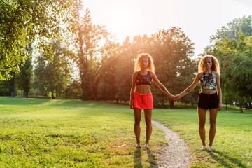 Twin sisters standing side by side in a park at backlight holding hands