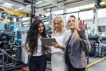 Three women with tablet talking in factory shop floor