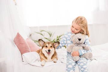 cute child sitting on bed with pembroke welsh corgi dog and teddy bear at home