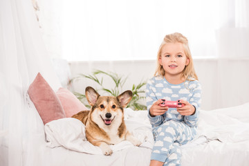 child sitting on bed with pembroke welsh corgi dog, holding joystick and playing video game at home