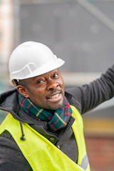 African American engineer wearing yellow protective workwear looking upwards among scaffolding