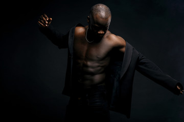Dark key portrait of sexy dancer man topless, with jacket on shoulders and chainlet on neck. Studio shot, black background