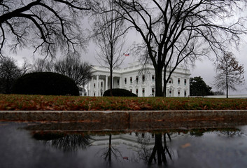 The White House is reflected in a puddle ahead of a potential partial government shut down over funding of a border wall in Washington