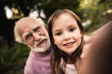 Little girl taking selfie with her grandpa
