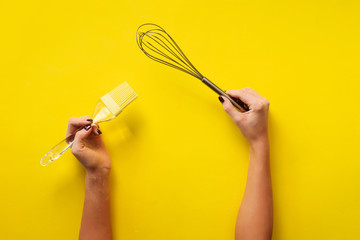 Wall Mural - Woman hand holding kitchen utensils on yellow background. Baking tools - brush, whisk, spatula. Bakery, cooking, healthy homemade food concept. Copy space
