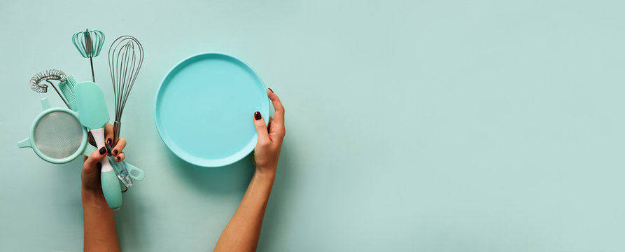 Baking flat lay. Female hands holding plate, kitchen tools, sieve, rolling pin, spatula and bruch on pastel blue background. Banner with copy space