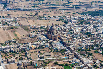 Rural Gozo island as seen from above. Aerial view of Gozo, Malta. The Rotunda of Xewkija (Casal Xeuchia) is the largest in Gozo island and its dome dominates the island everywhere.