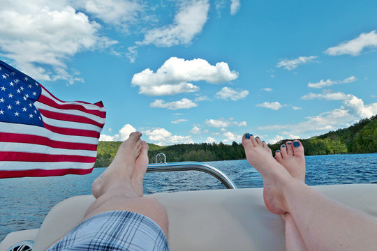 WIth a glimpse of the American flag, two people relax on a boat