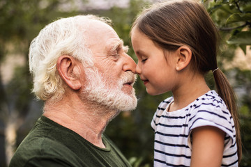 Little girl and her grandfather touch each other with their noses