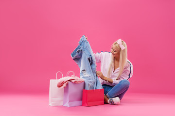 Sale concept. Young blonde woman pulls things out of bags and surprise considering the purchase after the sale in stores on pink studio background