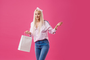 Portrait of an excited blond girl holding shopping bags  over pink background